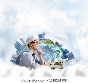 Side view of thoughtful man writer in hat and eyeglasses looking away and touching chin while using typing machine with Earth globe and cloudy skyscape on background. Elements of this image furnished