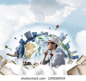 Side view of thoughtful man writer in hat and eyeglasses looking away and touching chin while using typing machine with flying books and Earth globe among cloudy skyscape on background. Elements of