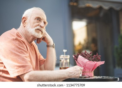 Side view of thoughtful mature male drinking tea in solitude. He is sitting at table with cup of hot drink and touching his face in consideration