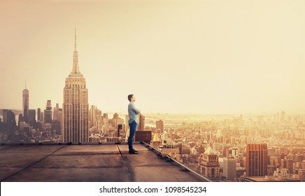 Side view of a thoughtful young businessman standing on concrete rooftop of a skyscraper watching over the big city at sunset. Business research concept.