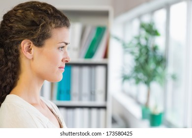 Side view of thoughtful young businesswoman in office