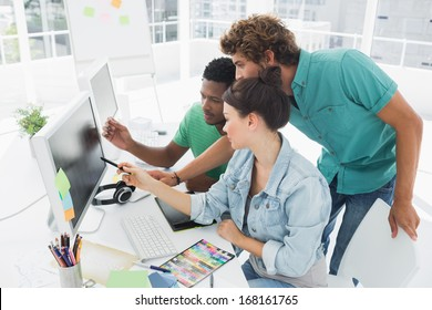 Side view of three artists working on computer at the office