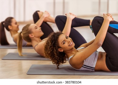 Side view of three attractive sport girls smiling while working out lying on yoga mat in fitness class. Beautiful Afro-American girl looking at camera