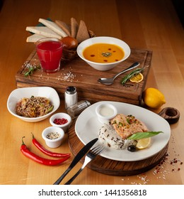 Side view of a three course meal, served on a wooden table: steamed salmon and rice, spicy pumpkin soup, thai noodles with vegetables, roasted chicken and sesame, flavoured with oyster sauce