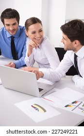 Side view of three people working on computer at office. Businesspeople sitting at desk in office and smiling