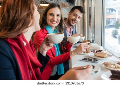 Side view of three young colleagues smiling happy while eating delicious cakes during break in a trendy coffee shop