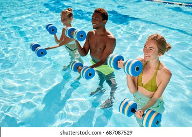 Side view - three young people two caucasian girls and an African American man doing aqua aerobic with dumbbells in swimming pool on warm summer day