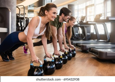 Side view of three young people smiling while doing the kettlebell plank challenge for strong core during group workout at the gym