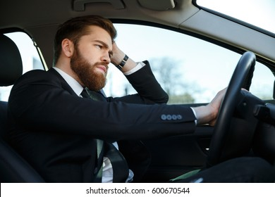 Side view of Tired bearded business man in suit driving car