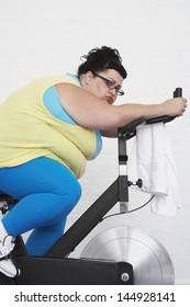 Side view of a tired overweight woman on exercise bike against white background