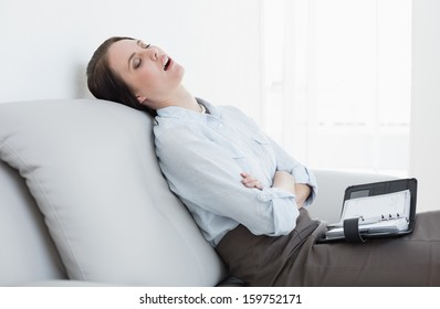 Side view of a tired well dressed young woman sitting and sleeping on sofa at home