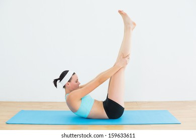 Side view of a toned young woman lying on her back and doing yoga in fitness studio