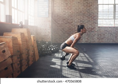 Side view of tough young woman exercising with kettle bell at gym. Fit female athlete doing crossfit workout at gym.