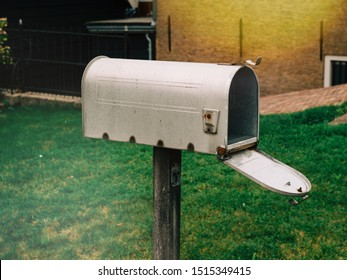 Side view of traditional american style open mailbox in front of the house with no letters or newspapers parcels inside