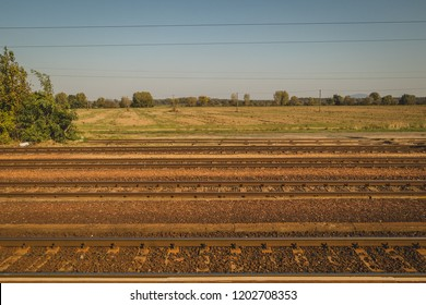 Side view of train tracks on a rural countryside in Hungary.