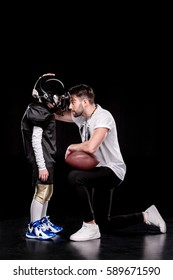 Side view of trainer instructing boy american football player isolated on black