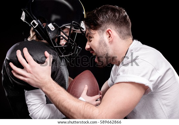 Side view of trainer screaming at boy american football player isolated on black
