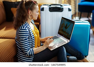 Side view of trendy solo traveller woman in striped jacket sitting near couch and trolley bags at modern home in sunny hot summer day buying plane tickets online on a laptop.