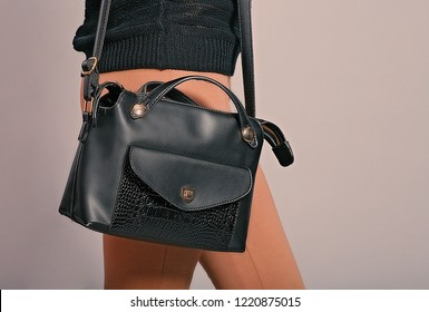 Side view of trendy woman with black hand bag hanging on her right shoulder studio shot, a lot of space for text