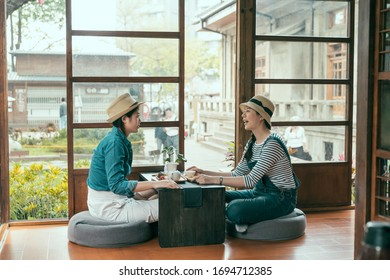 side view of two asian young girl travelers in straw hat travel in Tokyo Japan during spring time. happy female friends talking sitting in japanese architecture style house doing tea ceremony