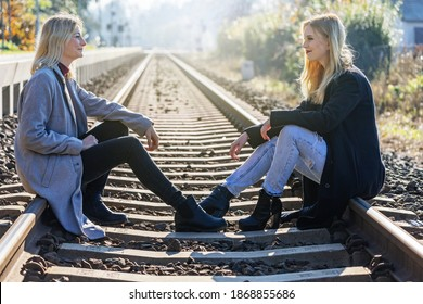 Side view of two attractive young women  sitting on rail and looking at each other in autumn backlight. Horizontally.