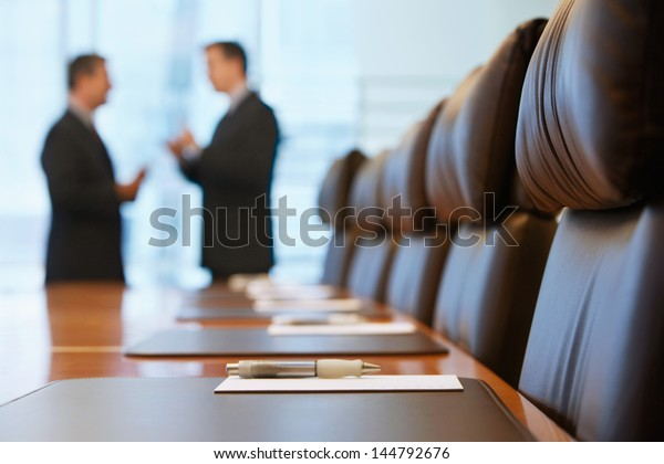 Side view of two blurred businessmen talking in conference room