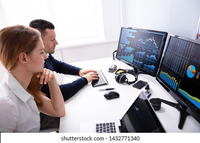 Side View Of Two Businesspeople Examining Graph On Computer At Workplace