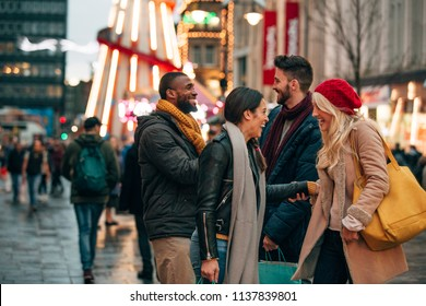 Side view of two couples meeting on a city street. Its winter and there is a fair ground ride on the street.
