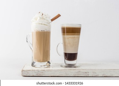Side view Two cups of Cappuccino and Chocolate Mocha with Cinnamon stick and whipped cream on top over wooden coaster