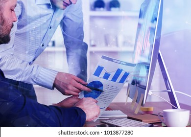 Side view of two european businessmen working on financial project at modern workplace with forex chart. Finance and trade concept. Double exposure