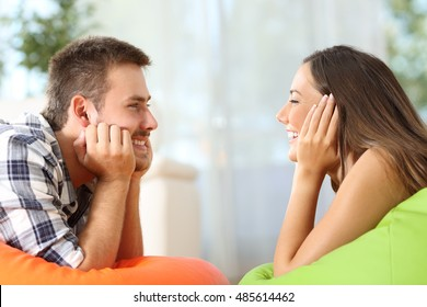 Side view of two friends falling in love looking each other lying on poufs in the living room at home