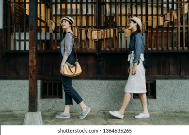 side view of two full length asian women traveler sightseeing visiting traditional japanese house walking in garden pathway by wooden window. kyoto religion shinto with wish hope card hanging on rope