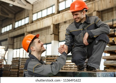 Side view of two laughing colleagues in orange hardhats and gray protective suits holding hands and looking at each other on metal stock. Smiling worker giving support hand to other, mood of teamwork.