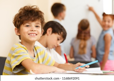 Side view of two little pupils sitting together at table and writing in copybook, one looking and smiling at camera. Smart classmates in process of learning new material in classroom.