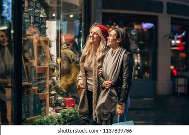 Side view of two mid adult women looking in a store window while doing some christmas shopping.