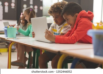 Side view of two mixed-race school boys looking at their laptop in classroom at school against two school girls doing same
