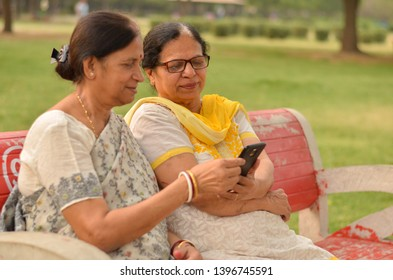Side view of two Senior Indian woman working on a mobile phone, experimenting with technology on a red park bench in an outdoor setting during summers wearing saree and salwar kameez in Delhi, India