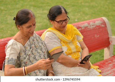 Side view of two Senior Indian woman working on mobile phone/tablet, experimenting with technology on a red park bench in an outdoor setting during summer wearing saree & salwar kameez in Delhi, India