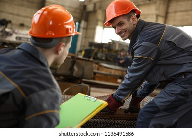 Side view of two workers of metal stock in uniform, orange helmets and protective gloves in process of work. Smiling man carrying springs and looking at his colleagues sitting near with clipboard.
