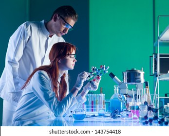 side view of two young caucasian scientists studying a molecular structure in a laboratory