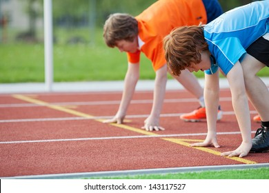 Side view of two young male runners on starting position at racetrack