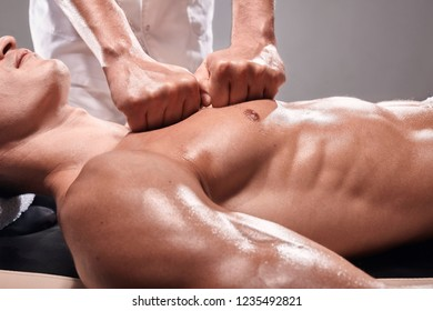 side view, two young man, 20-29 years old, sports physiotherapy indoors in studio, photo shoot. Masseur massaging athlete mans chest, muscular body, hands close-up.