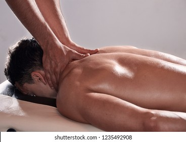 side view, two young man, 20-29 years old, sports physiotherapy indoors in studio, photo shoot. Physiotherapist massaging relaxed patient neck back side, with his hands.