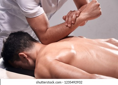 side view, two young man, 20-29 years old, sports physiotherapy indoors in studio, photo shoot. Strong Physiotherapist hard massaging relaxed patient neck back side, with his elbow.