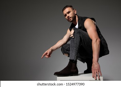 Side view of and uncertain young man pointing and squatting on a chair while wearing jeans and a jeans vest on gray studio background