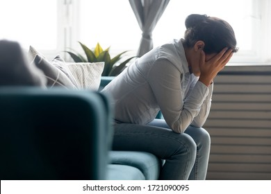 Side view unhappy depressed young indian girl hiding face in hands, sitting on sofa alone at home. Desperate millennial mixed race woman suffering from personal life problems or stress, headache.