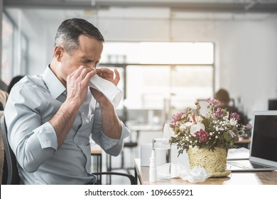 Side view unhappy ill businessman with running nose working with laptop in office. He sitting at table near pretty bouquet. Diseased employer at job concept