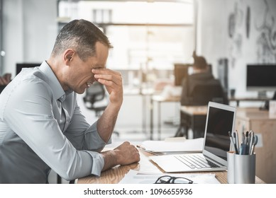 Side view unhappy weary employer rubbing eyes after long work with laptop. He situating at desk. Fatigue at job concept