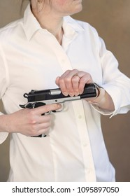 Side view of an unidentified woman holding a gun
