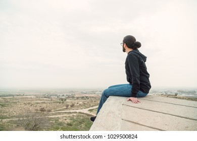 Side view unidentified young man in casual clothes and glasses sits on the high rock and looks at beautiful desert view and admires the nature